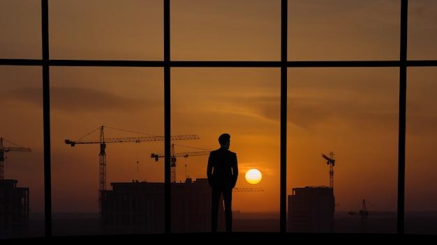 De man die bij het panoramische raam staat op de bouwconstructieachtergrond