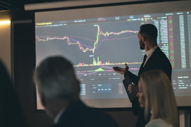 De man die bij het scherm staat op de zakelijke bijeenkomst