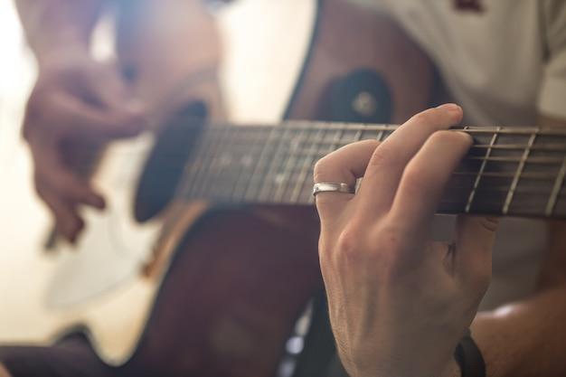 De man die de akoestische gitaar speelt