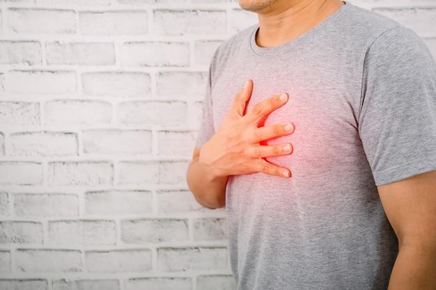 De man die de borst op het hart houdt symptomen van hartaandoeningen