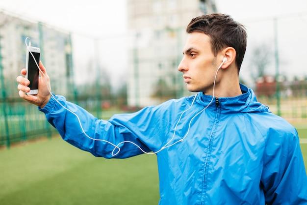 De man die luistert maakt een selfie tijdens een training. een jonge man sport, rent op het voetbalveld. de man werkt in de open lucht.