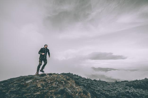 De man die op de berg loopt op een prachtige wolkenachtergrond