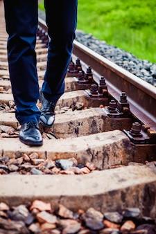 De man die op de spoorbielzen loopt