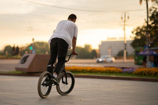 De man, die op volle hoogte staat, rijdt op een bmx-fiets. voor elk doel.