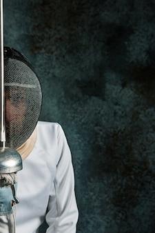 De man die schermkostuum met zwaard tegen grijs draagt
