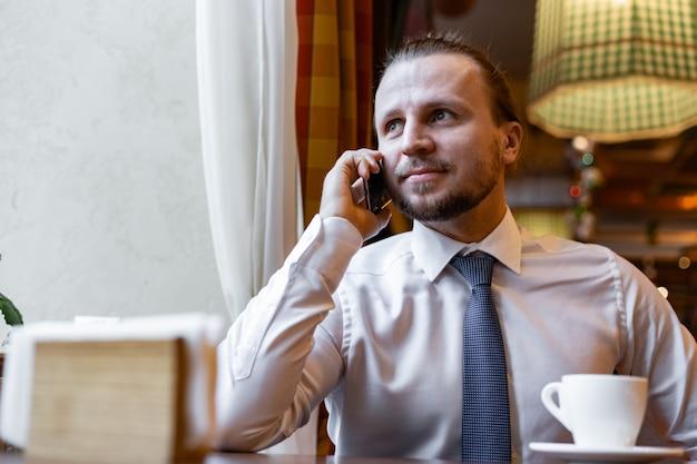 De man die van hanhsome de zitting van de celtelefoon in de koffie het binnen dragen in wit overhemd uitnodigt