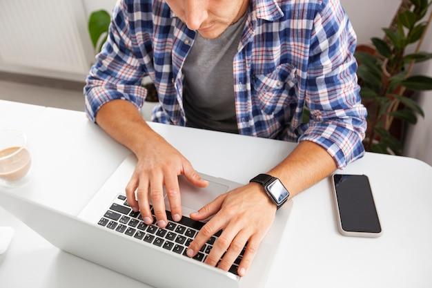 De man die vanuit huis online met een laptop werkt.