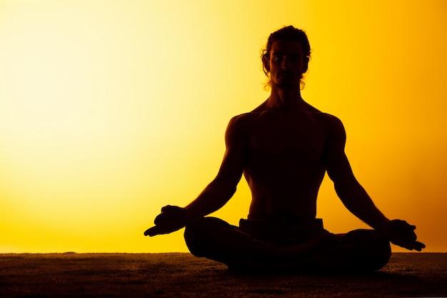 De man die yoga in het zonsonderganglicht uitoefenen