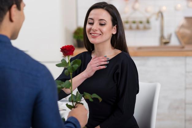 De man die zijn vriendin aanbiedt, is een roos