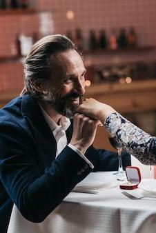 De man doet een huwelijksaanzoek en gaat de hand van een vrouw kussen in een restaurant