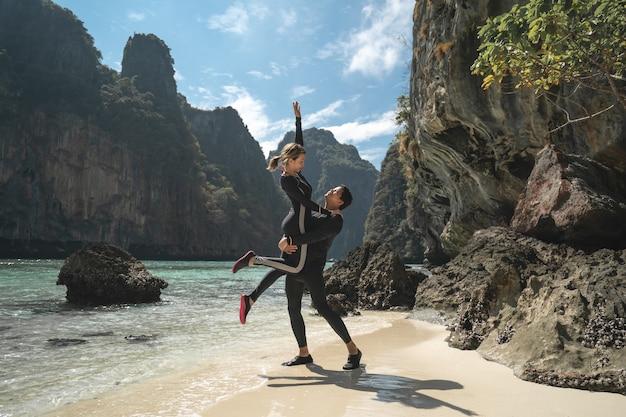 De man draagt de vrouw in zijn armen op het strand van phi phi en geniet van een mooie zomervakantie. reizen vakantie levensstijl concept
