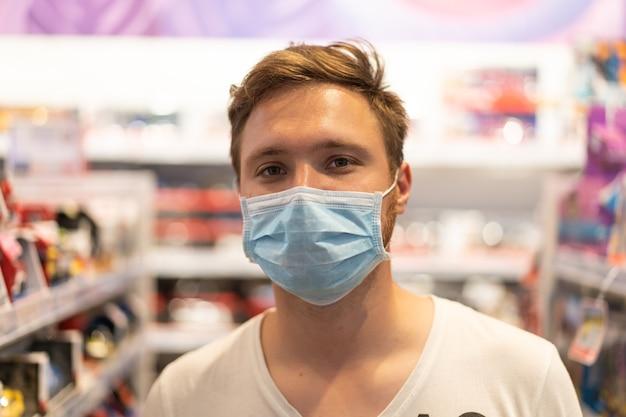 De man draagt een beschermend masker in de winkel. veiligheid, bescherming van de gezondheid tijdens covid-19 quarantaine.