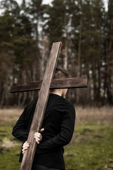 De man draagt het kruis. draag het kruis. de mens gelooft in god. hoop op allah.