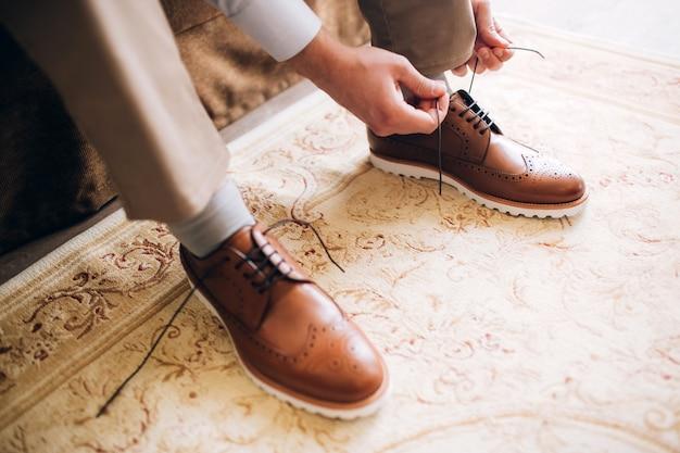 De man draagt schoenen. bind de veters aan de schoenen. heren stijl. beroepen. ter voorbereiding op het werk, naar de vergadering.