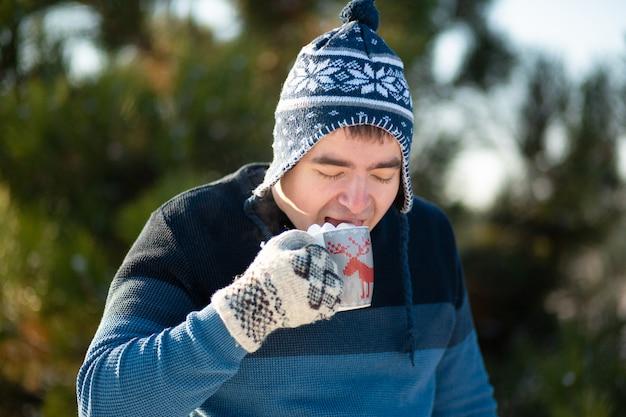 De man drinkt een warm drankje met marshmallows in de winter in het bos, een gezellige winterwandeling door het bos met een warm drankje, er is marshmallow uit een mok met een drankje, grappige foto