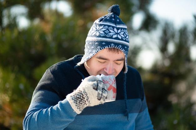 De man drinkt een warme drank met marshmallows in de winter in het bos. een gezellige winterwandeling door het bos met een warm drankje. er is marshmallow uit een mok met een drankje. grappige foto
