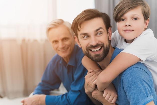 De man, een jongen en een oude man poseren op een grijze bank