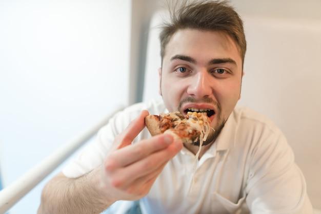 De man eet een heerlijke pizza. fast food voor lunch.
