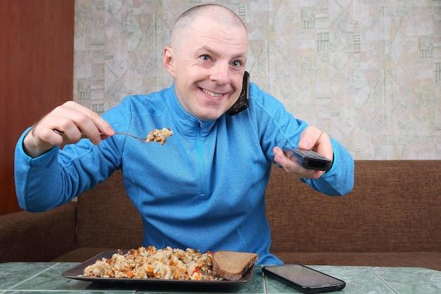 De man eet rijstpilaf en staart naar een tv-programma