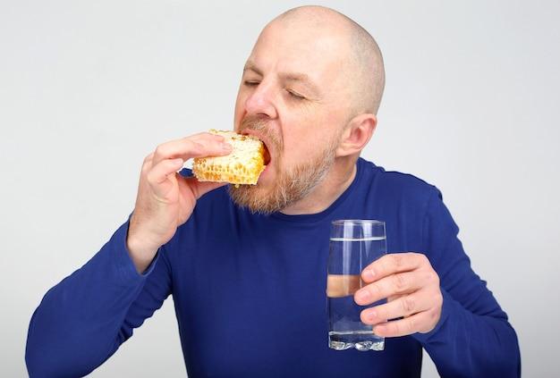 De man eet smakelijk en eet honing
