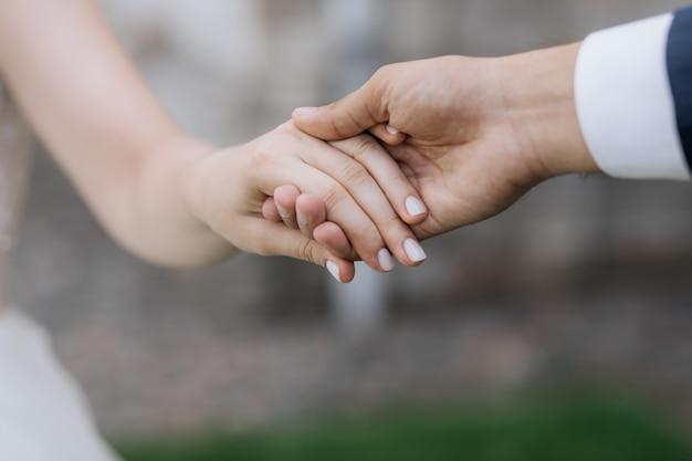 De man en de vrouw houden elkaar in openlucht samen handen