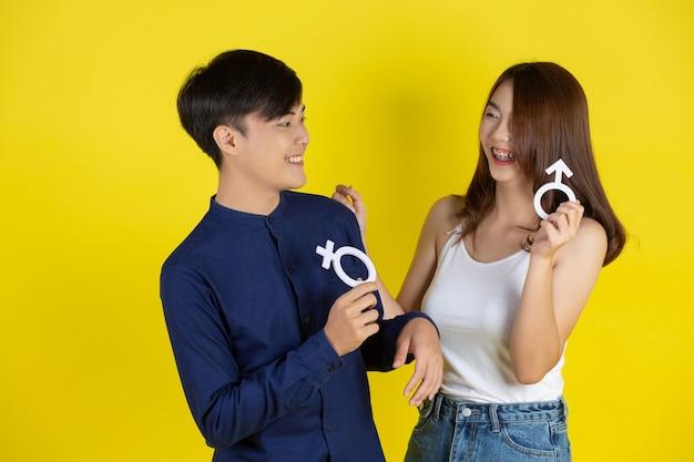 De man en het meisje houden een mannelijk en vrouwelijk symbool op een gele muur