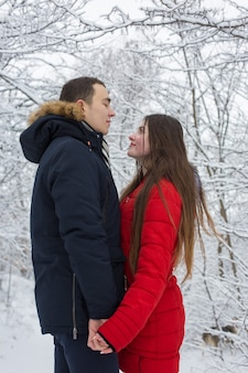 De man en het meisje rusten uit in het winterbos man en vrouw in de sneeuw jong stel