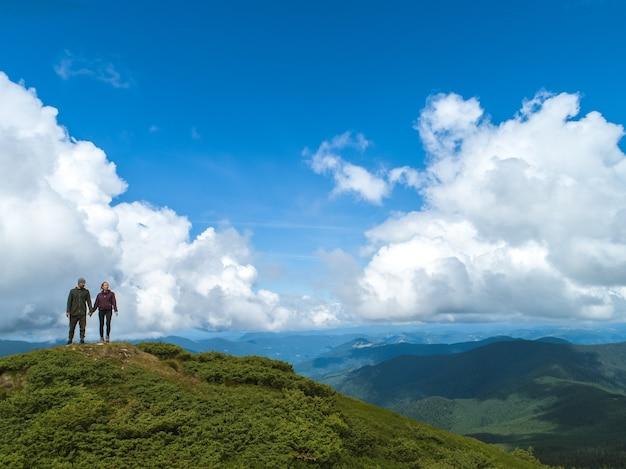 De man en vrouw die op een berg staan tegen het wolkenlandschap