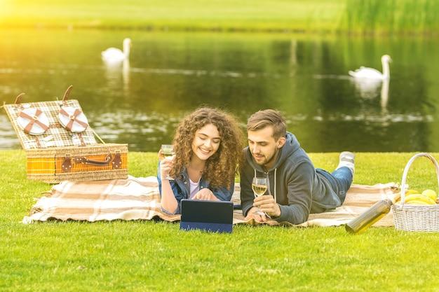 De man en vrouw drinken een wijntje bij de rivier