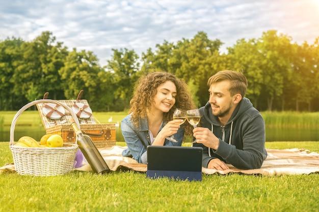 De man en vrouw drinken een wijntje bij het meer
