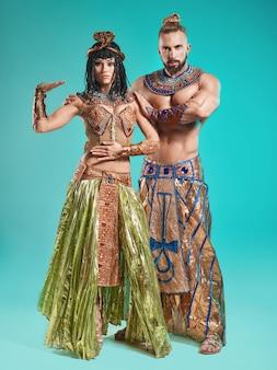 De man en vrouw in de beelden van de egyptische farao en cleopatra op blauwe studioachtergrond