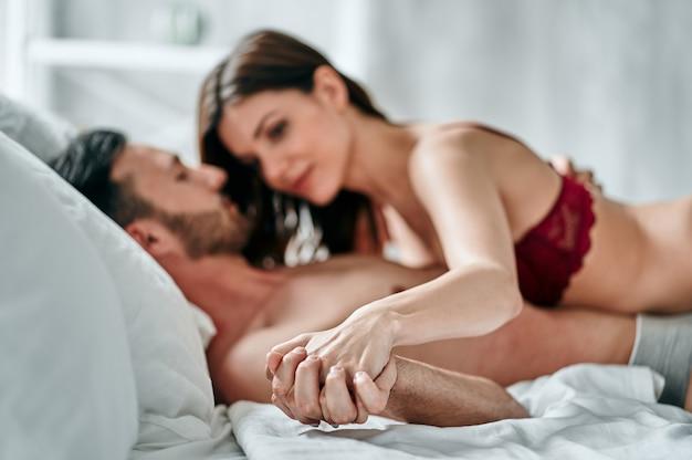 De man en vrouw in ondergoed hand in hand en liggend op het bed