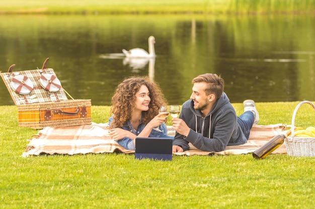 De man en vrouw lagen op het gras en drinken een wijntje op de achtergrond van de rivier