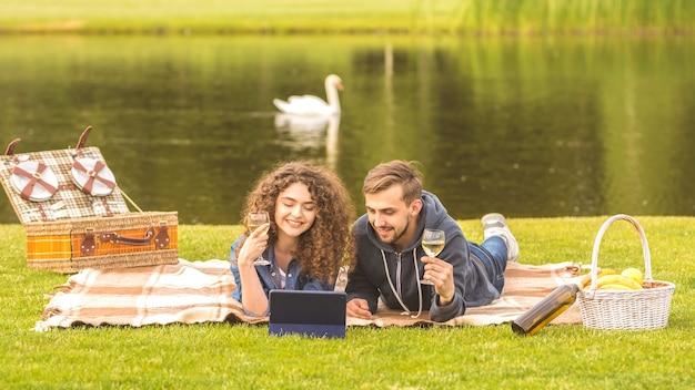 De man en vrouw met een tablet leggen en drinken een wijn