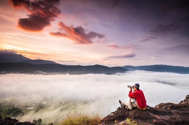 De man fotografeert de zee van mist op de hoge berg.