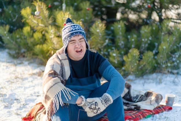 De man gaapt terwijl hij in een winterbos zit, gewikkeld in een warme, gezellige plaid