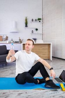 De man gaat thuis sporten. atleet drinkt water terwijl hij thuis op de grond zit, gezonde levensstijl