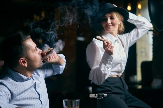 De man-gangster en de mooie senior vrouw die sigaar rookt in een bar