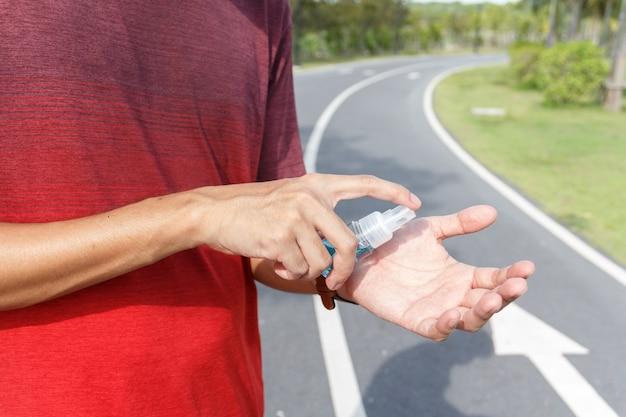 De man gebruikt alcohol om handen schoon te maken ter voorkoming van een uitbraak van het coronavirus. coivd 19