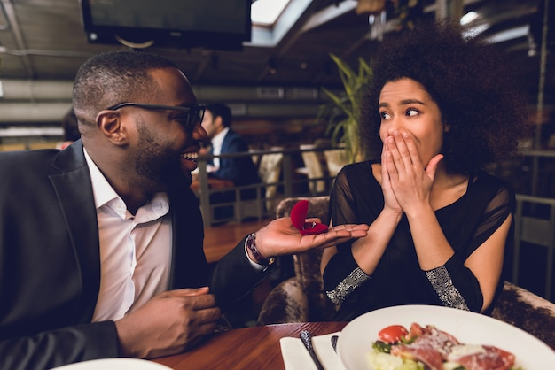 De man geeft de ring aan het meisje.