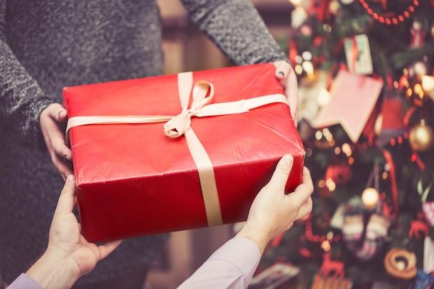 De man geeft een grote rode geschenkdoos aan een vrouw tegen een geweldige kerstboom.