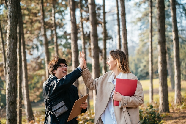 De man geeft hoge vrouw vijf in het bos