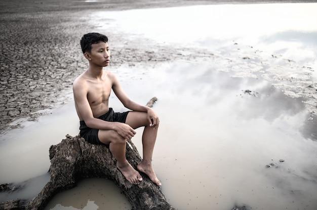 De man ging op de voet van de boom zitten, legde zijn handen op zijn knieën en keek vooruit.