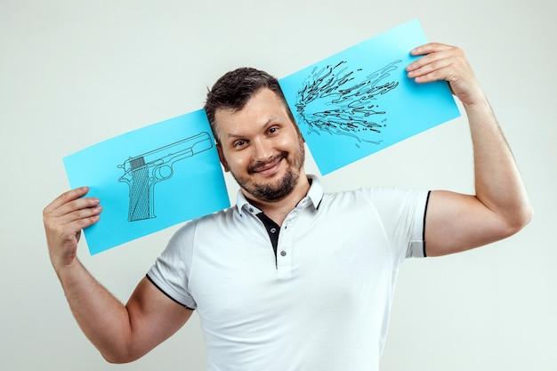 De man glimlacht en houdt in zijn handen een blauw laken met aan de ene kant een beschilderd pistool en aan de andere kant een blik van bloed.