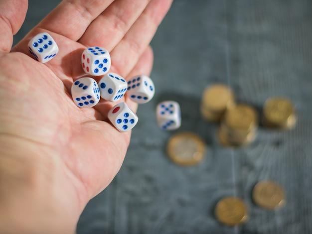 De man gooit het spel dobbelstenen op de tafel met munten. geld- en spelblokjes.