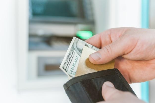 De man haalt een bankkaart met geld uit zijn portemonnee. tegen de achtergrond van een geldautomaat.