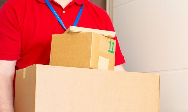 De man heeft afgeleverd en houdt kartonnen dozen vast. snelle en gratis verzending. online winkelen en express levering. quarantaine