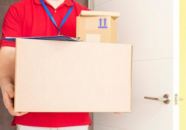 De man heeft afgeleverd en houdt kartonnen dozen vast. snelle en gratis verzending. online winkelen en express levering.