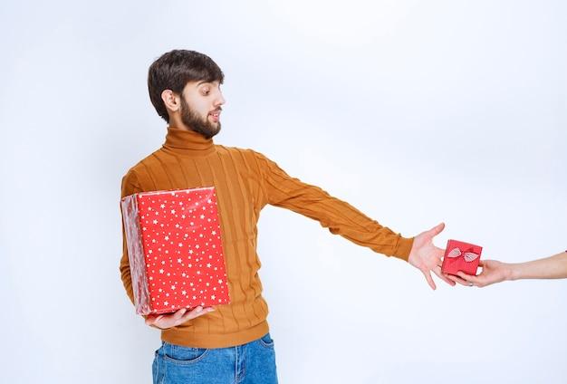 De man heeft een grote rode geschenkdoos en verlangt ernaar om nog een kleine te nemen.