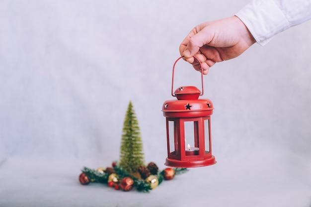 De man heeft een lamp met kaarsen in zijn handen
